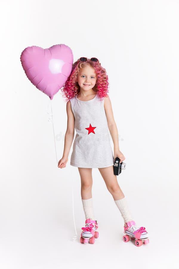 Τρίχες Colores Πορτρέτο του αστείου κοριτσιού μόδας hipster με ρόδινο ballon με μορφή της καρδιάς Αναδρομική κάμερα στο χέρι της στοκ εικόνα