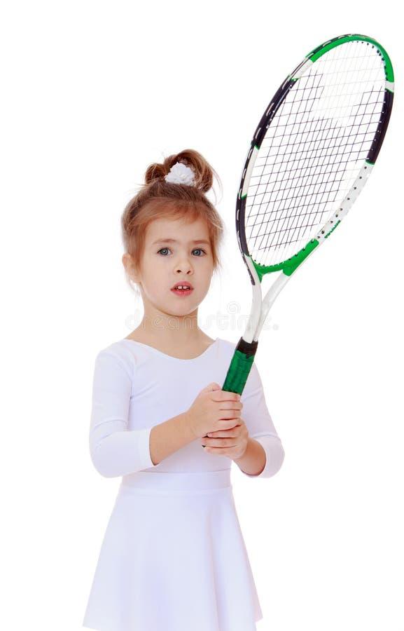 Τρίχρονο κορίτσι με μια ρακέτα αντισφαίρισης υπό εξέταση στοκ εικόνα