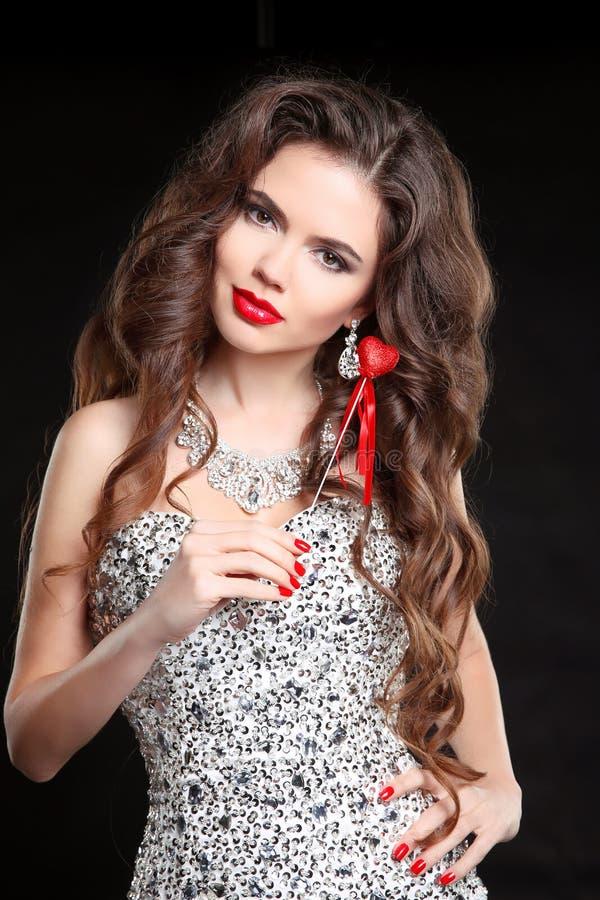 τρίχωμα μακρύ Η όμορφη γυναίκα με τα κόκκινα χείλια, τα καρφιά Brune στοκ φωτογραφία
