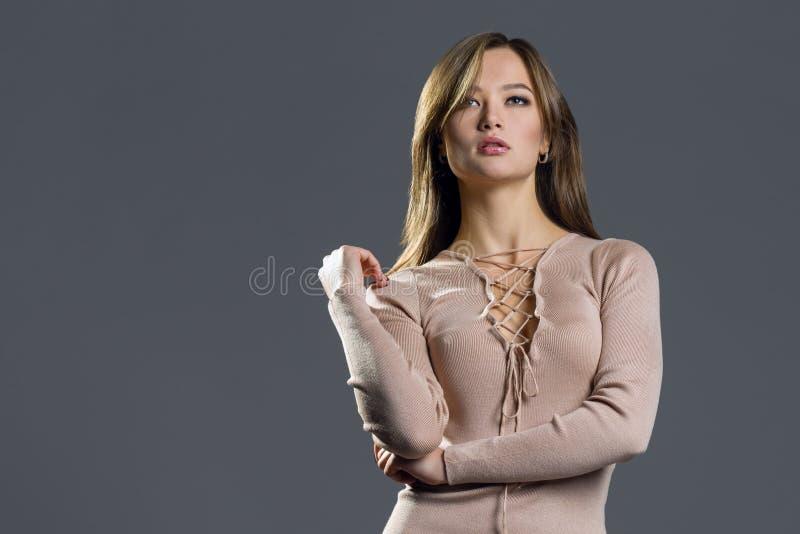 τρίχωμα Πρότυπη γυναίκα μόδας ομορφιάς σχετικά με τη μακριά και υγιή καφετιά τρίχα της Κορίτσι brunette ομορφιάς στο γκρι στοκ εικόνα