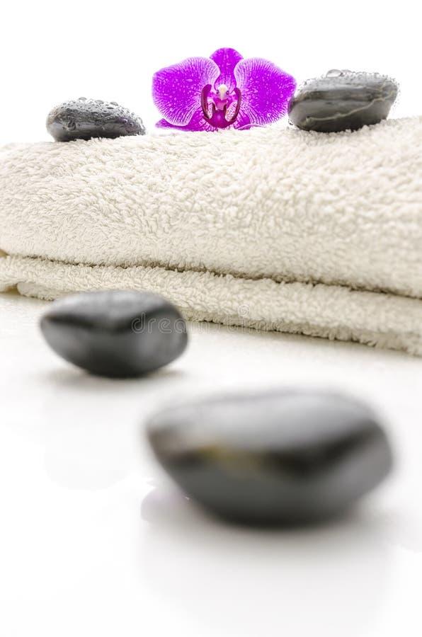 Τρίψτε τις πέτρες και το ιώδες orchid λουλούδι σε μια πετσέτα στοκ φωτογραφία με δικαίωμα ελεύθερης χρήσης