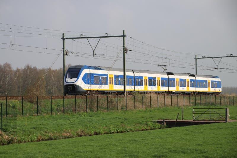 Τραίνο του NS, ολλανδικοί σιδηρόδρομοι, sprinter στη διαδρομή μεταξύ του γκούντα και του Ρότερνταμ στα λιβάδια Moordrecht στοκ εικόνα