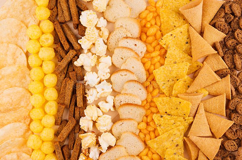 Τραγανά πρόχειρα φαγητά κατατάξεων - popcorn, nachos, croutons, ραβδιά καλαμποκιού, τσιπ πατατών ως διακοσμητικό υπόβαθρο, τοπ άπ στοκ φωτογραφία με δικαίωμα ελεύθερης χρήσης