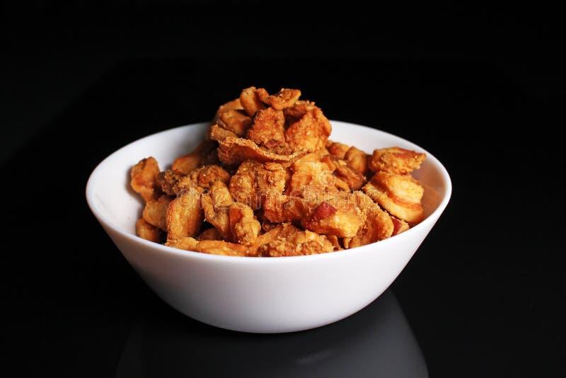 Τραγανή τηγανισμένη τριξίματα κρούστα λαρδιού χοιρινού κρέατος υπολειμμάτων ζωϊκού λίπους στο μαύρο αντανακλαστικό υπόβαθρο στούν στοκ φωτογραφία με δικαίωμα ελεύθερης χρήσης