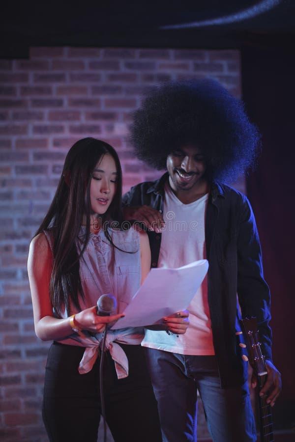 Τραγουδιστής με τα έγγραφα ανάγνωσης κιθαριστών στο φωτισμένο νυχτερινό κέντρο διασκέδασης στοκ φωτογραφία με δικαίωμα ελεύθερης χρήσης