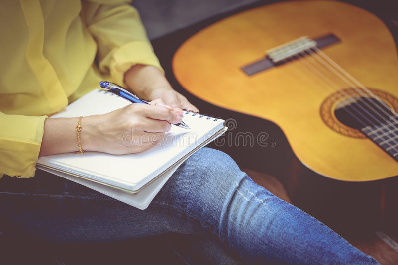 Τραγουδοποιός κινηματογραφήσεων σε πρώτο πλάνο που γράφει σε χαρτί σημειώσεων με το ακουστικό ΝΕ κιθάρων στοκ εικόνες με δικαίωμα ελεύθερης χρήσης