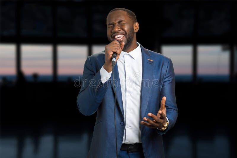 Τραγουδώντας άτομο στο υπόβαθρο βραδιού στοκ φωτογραφία