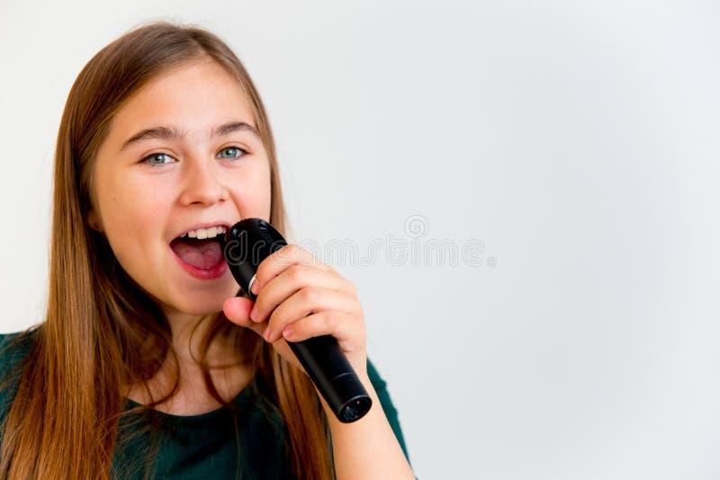 Τραγούδι κοριτσιών με ένα μικρόφωνο στοκ εικόνες