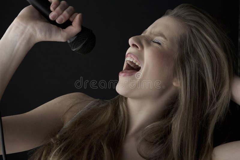 Τραγούδι έφηβη στο μικρόφωνο στοκ εικόνες