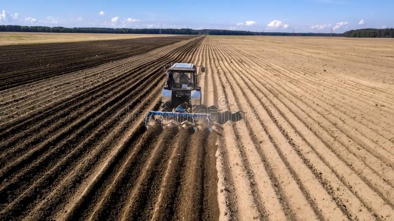 Τρακτέρ - εναέρια άποψη ενός τρακτέρ στην εργασία - που καλλιεργεί έναν τομέα την άνοιξη με το μπλε ουρανό - γεωργικά μηχανήματα στοκ εικόνες με δικαίωμα ελεύθερης χρήσης