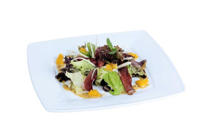 Τρανταγμένο βόειο κρέας, σαλάτα, μαρούλι, πορτοκάλι στο πιάτο στοκ εικόνα