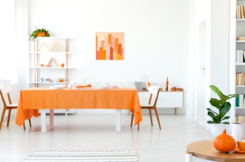 Τραπεζαρία στο ζωηρό χρώμα Πορτοκαλί τραπεζομάντιλο στο μακρύ πίνακα με τις άσπρες καρέκλες στοκ εικόνα με δικαίωμα ελεύθερης χρήσης