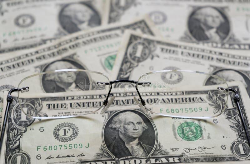 Τραπεζογραμμάτια ενός δολαρίων ως υπόβαθρο και γυαλιά στοκ φωτογραφίες