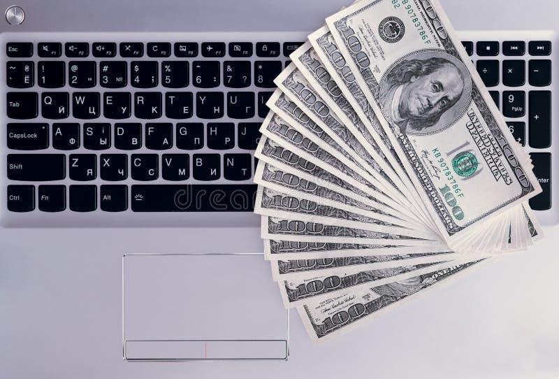 Τραπεζογραμμάτια πέρα από τα χρήματα δολαρίων πληκτρολογίων lap-top στοκ φωτογραφία