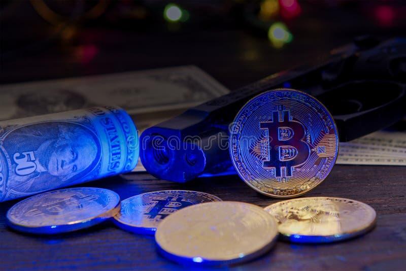 Τραπεζογραμμάτια Bitcoins και δολαρίων σε έναν πίνακα με το UV φως στοκ φωτογραφίες