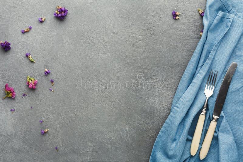 Τραπεζομάντιλο και μαχαιροπήρουνα στο γκρίζο επιτραπέζιο υπόβαθρο στοκ φωτογραφία με δικαίωμα ελεύθερης χρήσης