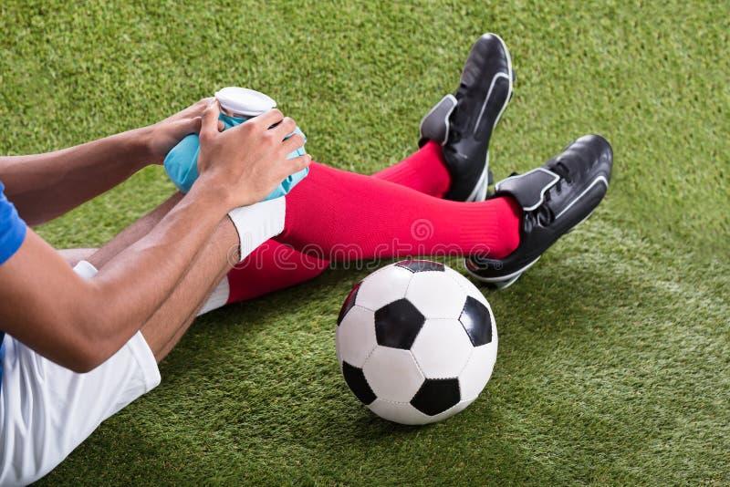 Τραυματισμένος ποδοσφαιριστής που εφαρμόζει το πακέτο πάγου στο γόνατο στοκ εικόνα με δικαίωμα ελεύθερης χρήσης