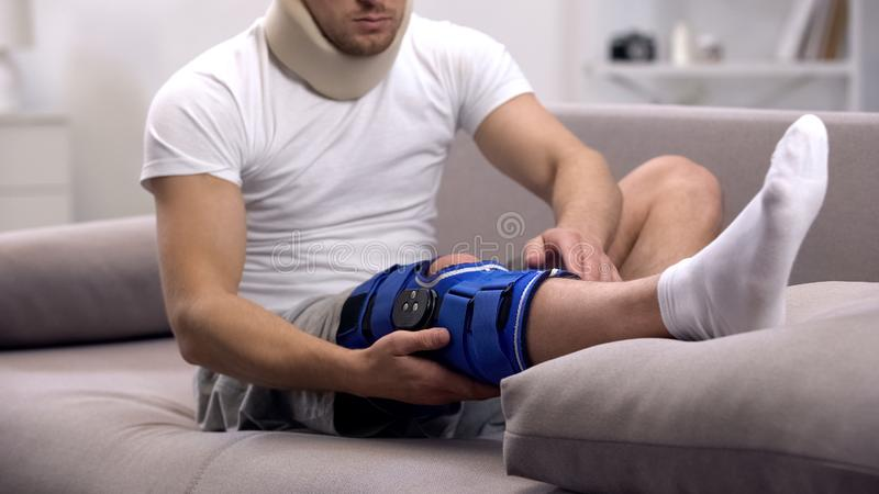 Τραυματισμένο άτομο στο αυχενικό περιλαίμιο αφρού που ελέγχει το στήριγμα γονάτων νεοπρενίου, αποκατάσταση στοκ εικόνες