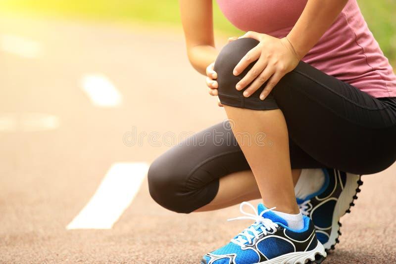 Τραυματισμένο δρομέας γόνατο γυναικών στοκ εικόνα