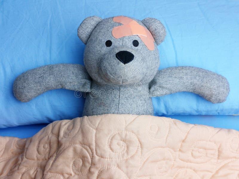 Τραυματισμένο Teddy αντέχει τα ασβεστοκονιάματα που στηρίζονται στο κρεβάτι στοκ εικόνες