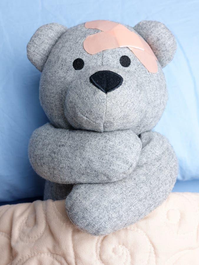Τραυματισμένο Teddy αντέχει το αγκάλιασμα κρεβατιών ασβεστοκονιαμάτων στοκ φωτογραφία με δικαίωμα ελεύθερης χρήσης