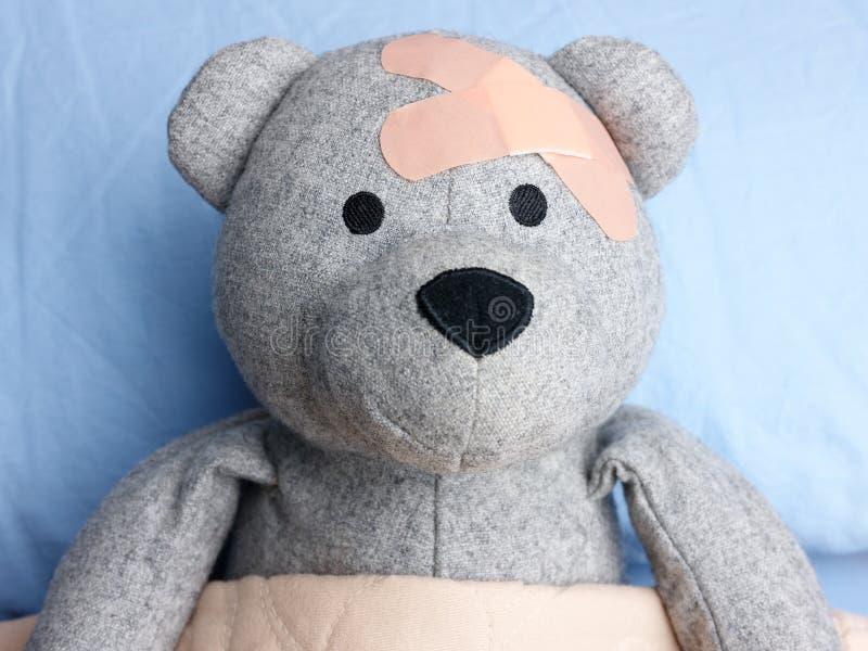 Τραυματισμένο Teddy αντέχει το επικεφαλής κρεβάτι ασβεστοκονιαμάτων στοκ εικόνες