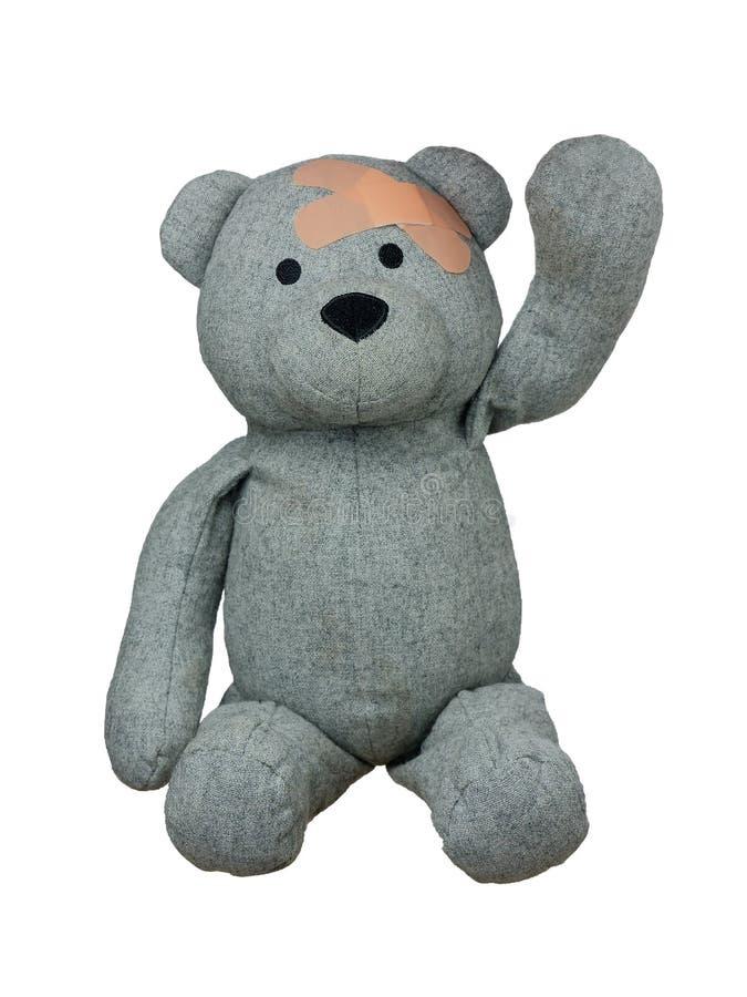 Τραυματισμένο Teddy αφορά με τα ασβεστοκονιάματα το επικεφαλής χέρι χαιρετισμών που απομονώνεται επάνω απεικόνιση αποθεμάτων