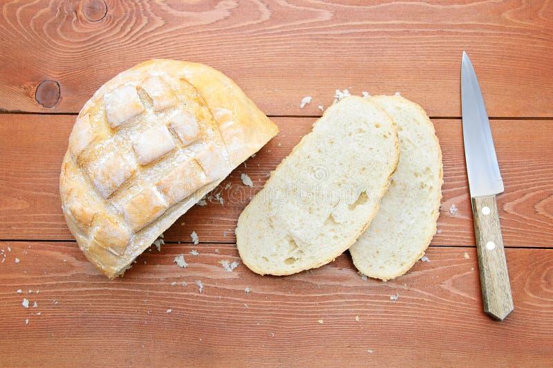 Τραχιά φραντζόλα του ψωμιού, μια φέτα του ψωμιού και ένα μαχαίρι Στο ξύλινο καφετί υπόβαθρο στοκ εικόνες με δικαίωμα ελεύθερης χρήσης