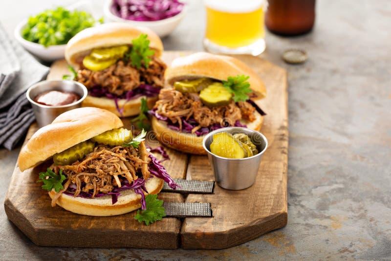 Τργμένα σάντουιτς χοιρινού κρέατος με το λάχανο και τα τουρσιά στοκ εικόνα