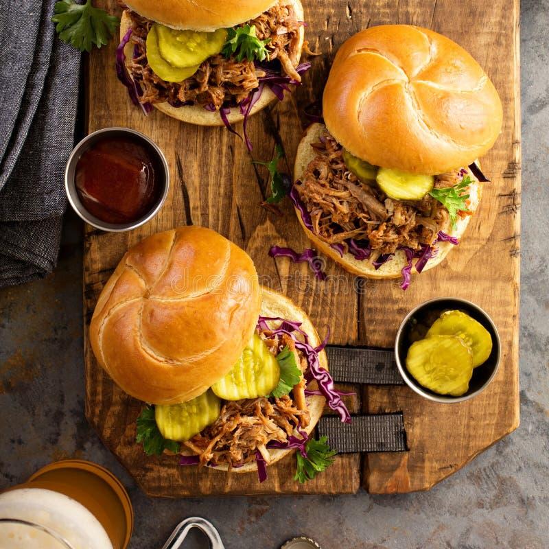Τργμένα σάντουιτς χοιρινού κρέατος με το λάχανο και τα τουρσιά στοκ εικόνες
