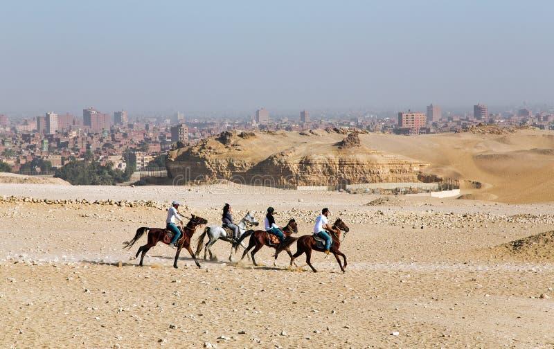 Τρεις άνδρες και άλογα ενός γύρου γυναικών στις πυραμίδες στοκ εικόνες