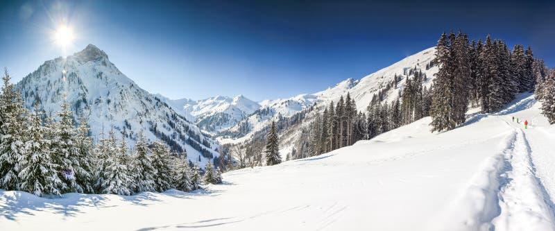 Τρεις άνθρωποι που στο χειμερινό τοπίο βουνών με το βαθύ χιόνι τη σαφή ηλιόλουστη ημέρα Allgau, Βαυαρία, Γερμανία στοκ εικόνες