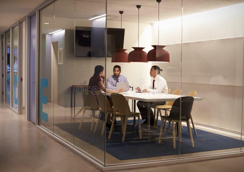 Τρεις άνθρωποι στο θαλαμίσκο συνεδρίασης σε μια μεγάλη εταιρική επιχείρηση στοκ φωτογραφία
