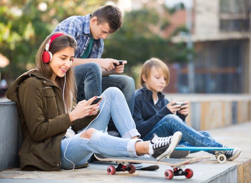 Τρεις έφηβοι με τα τηλέφωνα υπαίθρια στοκ φωτογραφίες με δικαίωμα ελεύθερης χρήσης