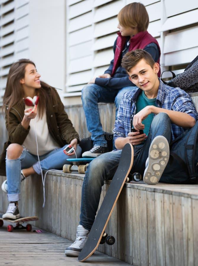Τρεις έφηβοι με τα smartphones υπαίθρια στοκ φωτογραφία
