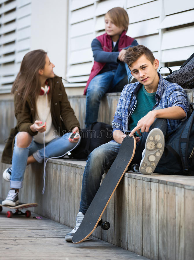Τρεις έφηβοι με τα smartphones υπαίθρια στοκ εικόνες με δικαίωμα ελεύθερης χρήσης