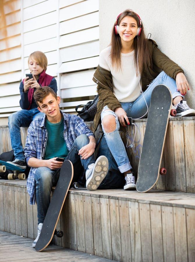 Τρεις έφηβοι με τα smartphones στοκ φωτογραφίες