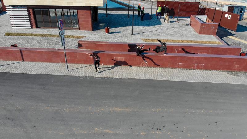 Τρεις αθλητικοί νεαροί άνδρες που υπερνικούν τα εμπόδια και που τρέχουν στο δρόμο Εναέρια άποψη στοκ φωτογραφίες με δικαίωμα ελεύθερης χρήσης