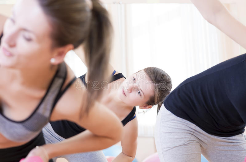 Τρεις αθλητικές καυκάσιες ενεργές γυναίκες που κάνουν τις τεντώνοντας ασκήσεις με Barbells στη γυμναστική στοκ εικόνες