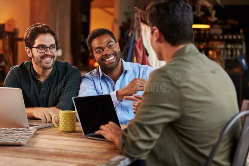 Τρεις αρσενικοί σχεδιαστές μόδας στη συνεδρίαση που χρησιμοποιεί το lap-top στοκ φωτογραφίες με δικαίωμα ελεύθερης χρήσης