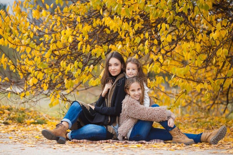 Τρεις αδελφές στον περίπατο στο πάρκο φθινοπώρου στοκ εικόνες