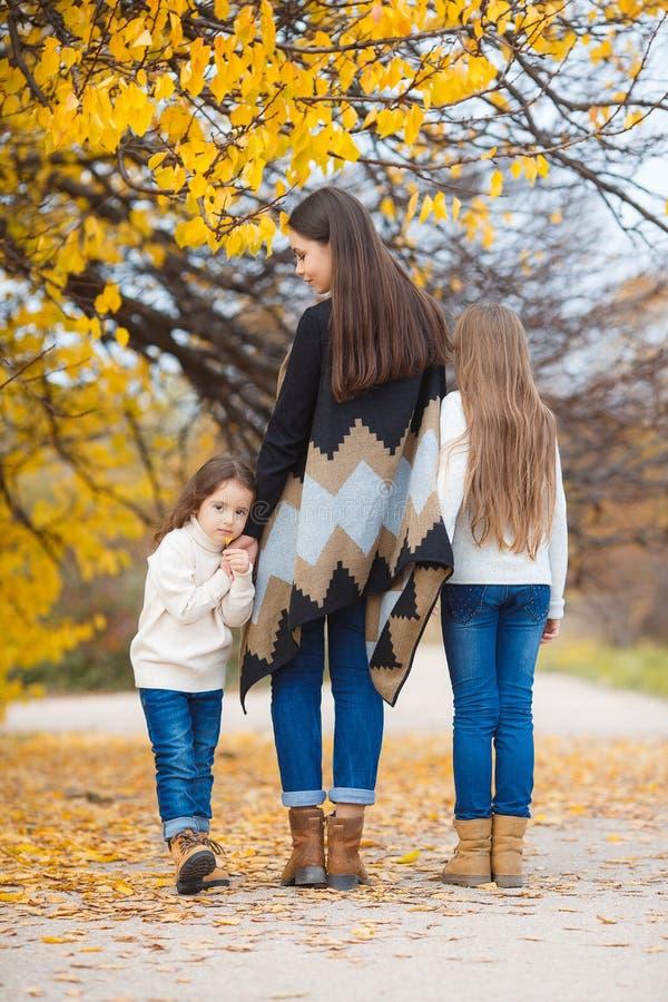 Τρεις αδελφές στον περίπατο στο πάρκο φθινοπώρου στοκ φωτογραφία