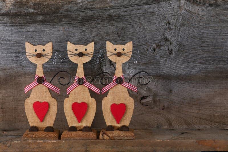 Τρεις βαλεντίνοι αγαπούν τις ξύλινες μορφές γατών με την κόκκινη καρδιά Decoratio στοκ φωτογραφίες