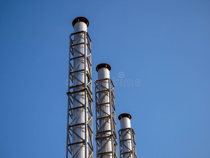 Τρεις βιομηχανικές καπνοδόχοι κλείνουν αυξημένος, στοκ φωτογραφία