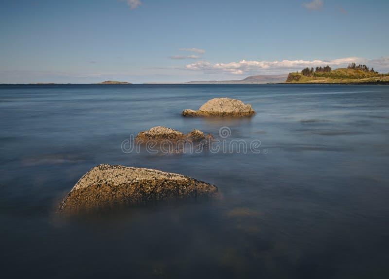 Τρεις βράχοι στον ωκεανό που οδηγεί πέρα από το νερό προς ένα απόμακρο νησί στη μακροχρόνια έκθεση οριζόντων στοκ εικόνα