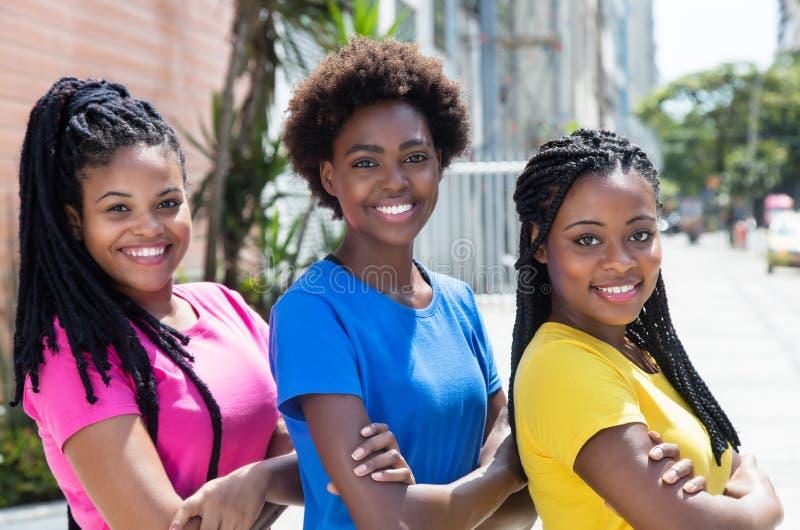 Τρεις γελώντας φίλες αφροαμερικάνων στη γραμμή στην πόλη στοκ εικόνες