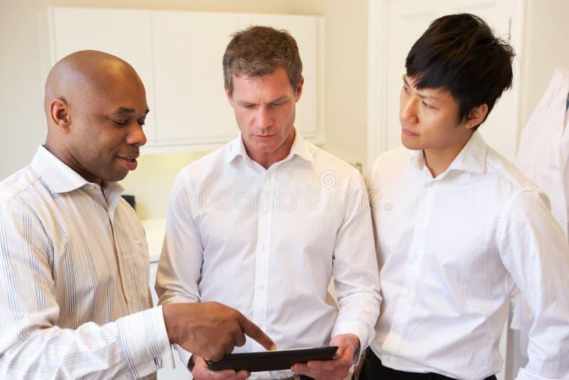 Τρεις γιατροί που διοργανώνουν τη συζήτηση που χρησιμοποιεί την ψηφιακή ταμπλέτα στοκ εικόνες με δικαίωμα ελεύθερης χρήσης