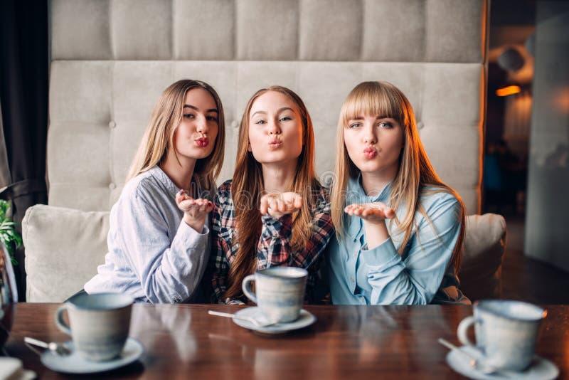 Τρεις ελκυστικές φίλες φυσούν ένα φιλί στον καφέ στοκ εικόνες