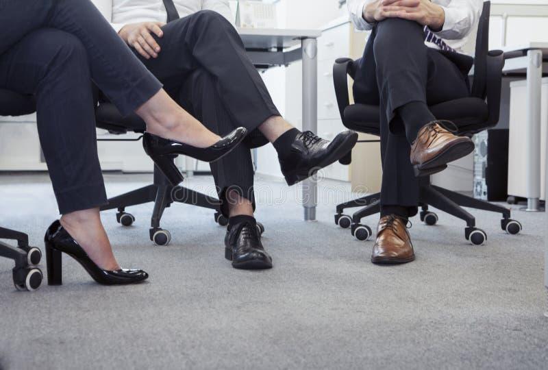 Τρεις επιχειρηματίες με διασχισμένη την πόδια συνεδρίαση στις καρέκλες, χαμηλό τμήμα στοκ εικόνες
