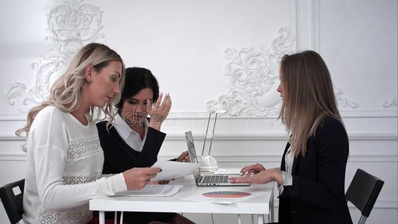 Τρεις επιχειρησιακές γυναίκες που εργάζονται στο γραφείο και που συζητούν κάτι στοκ φωτογραφία με δικαίωμα ελεύθερης χρήσης